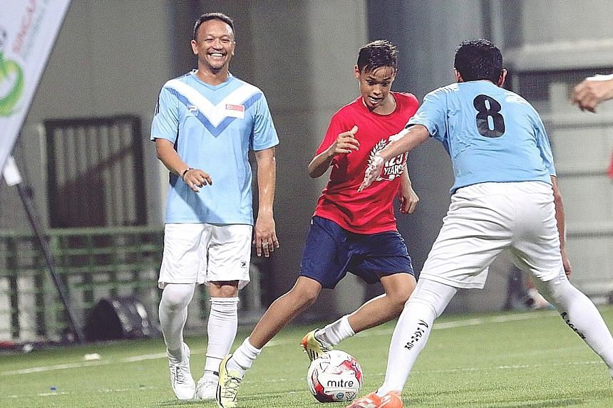 Former Singapore national football captain Fandi Ahmad watching his son Ilhan take on a defender during a friendly between ex-Singapore internationals and a team comprising celebrities and fans. The friendly, organised by the Football Association of