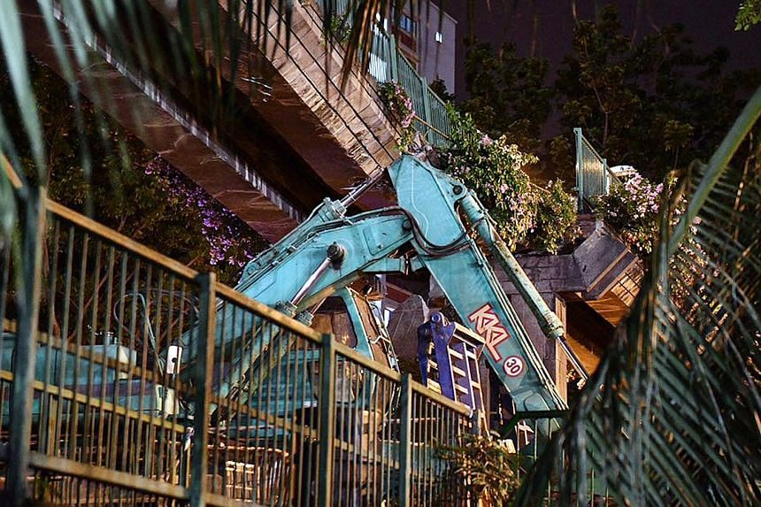 By 7.30am, the main section of the bridge was removed, leaving its middle pylon and staircase structures, allowing traffic to resume. The scene of the accident on Friday night, where the arm of an excavator being ferried on a trailer hit a pedestrian