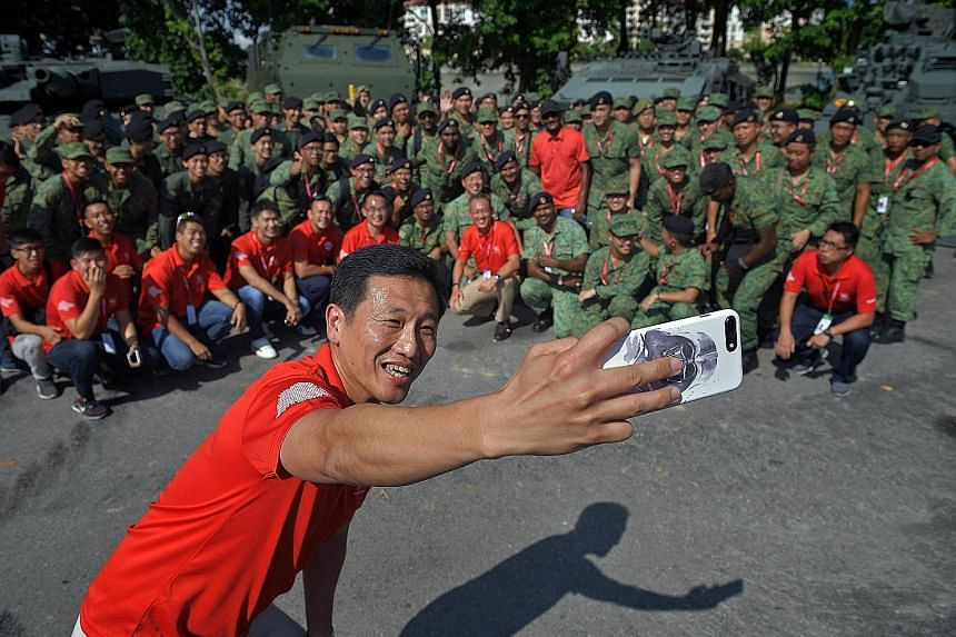 Mr Ong Ye Kung taking a wefie with the participants of the Dynamic Defence Display at the F1 Village yesterday. The minister was visiting NDP participants and staff at the preview show, during which he said that The Float @ Marina Bay has been one of