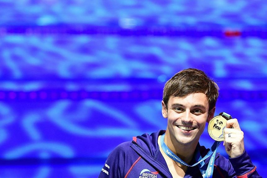 Tom Daley celebrates winning the gold medal after the podium ceremony for the Men's 10m plaform final at the 2017 FINA World Championships.
