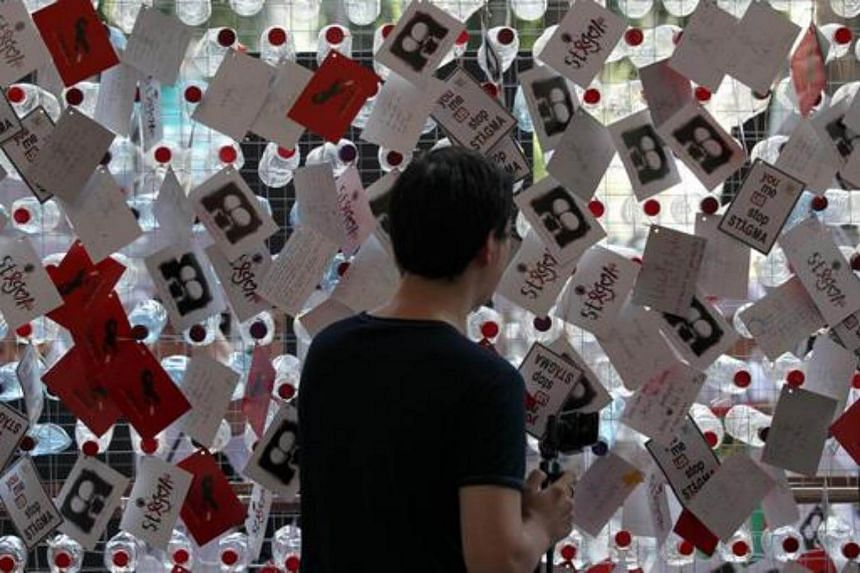 A visitor reads postcards showing support for HIV positive sufferers during a World Aids Day campaign in Kuala Lumpur.