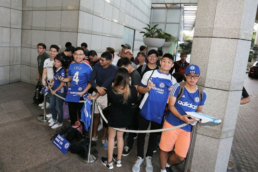 Chelsea fans queue up to catch a glimpse of the team at the Ritz-Carlton hotel.