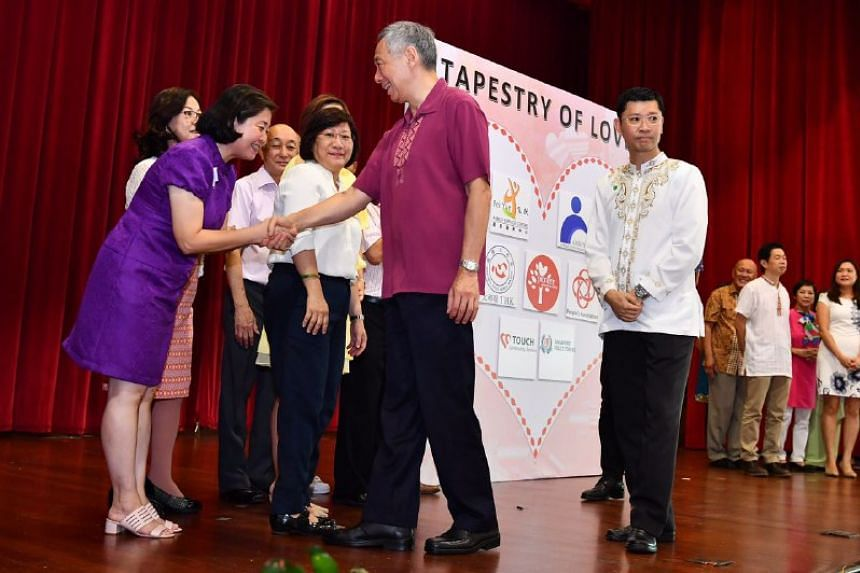 Prime Minister Lee Hsien Loong shaking hand with Ms Tan Guat Hoong, a Pioneer Generation Ambassador.