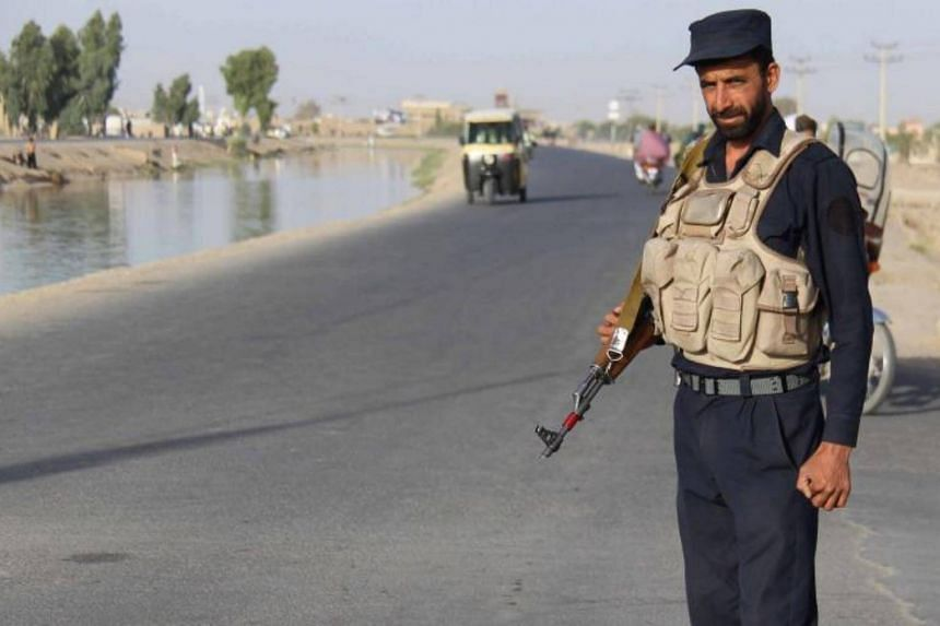 Afghan Police stand guard on a highway leading to Shah Wali Khan district, in Kandahar, on July 22, 2017.