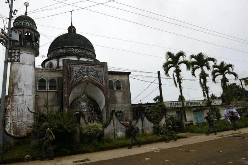 Philippine Marines walk past a mosque during a patrol along a deserted street at the frontline in Marawi, on July 22, 2017.