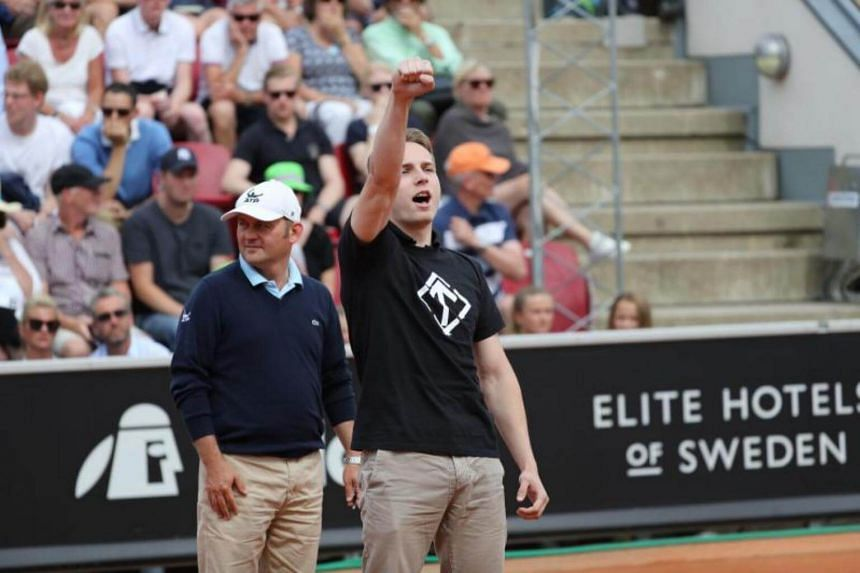 A man raises his arm in a Nazi-like salute after walking on the court during the Swedish Open semifinal match between Fernando Verdasco and David Ferrer, on July 22, 2017.