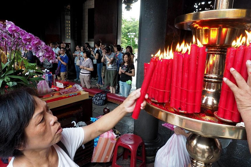 A woman lights a candle at the Buddhist Longshan Temple as members of religious groups stage a protest against the alleged plan to ban burning incense in temples, in Taipei, on July 23, 2017.