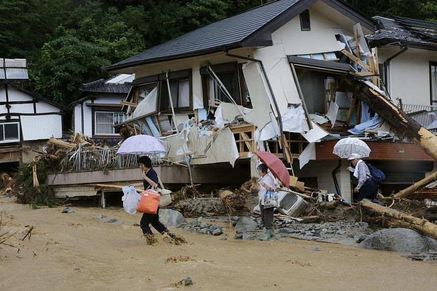 Residents cross a flooded stream as they evacuate from a makeshift evacuation center in Asakura, Fukuoka Prefecture, on July 7, 2017.