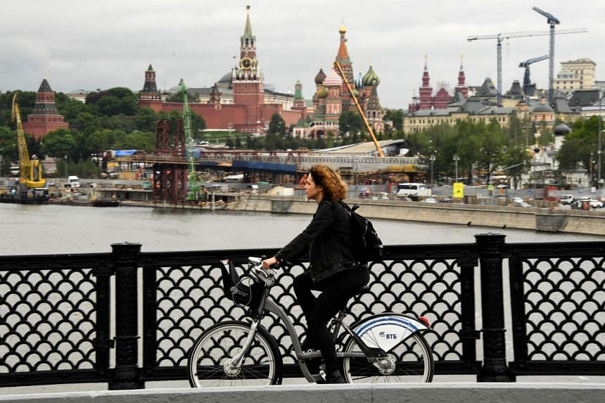 A woman riding a bicycle along a bridge over the Moskva river in central Russia.