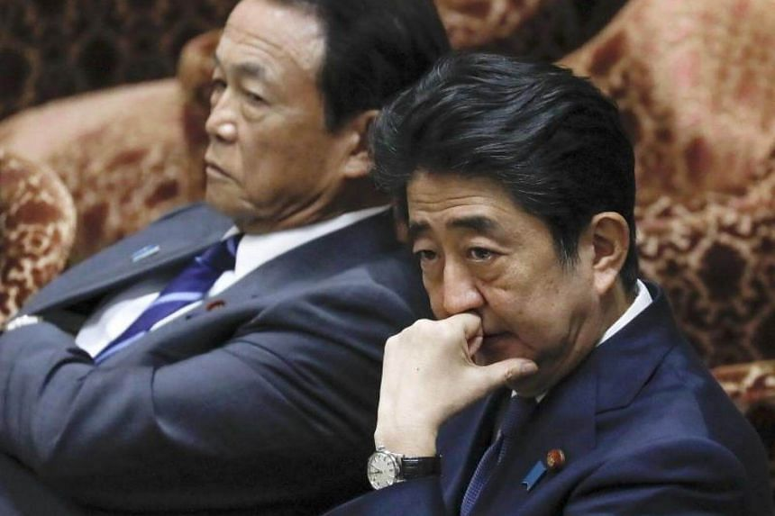 Japanese Prime Minister Shinzo Abe (right) listens to an opposition Parliament Member as Finance Minister Taro Aso (left) looks on during a special parliamentary committee at the Lower House in Tokyo, Japan, on July 24, 2017.