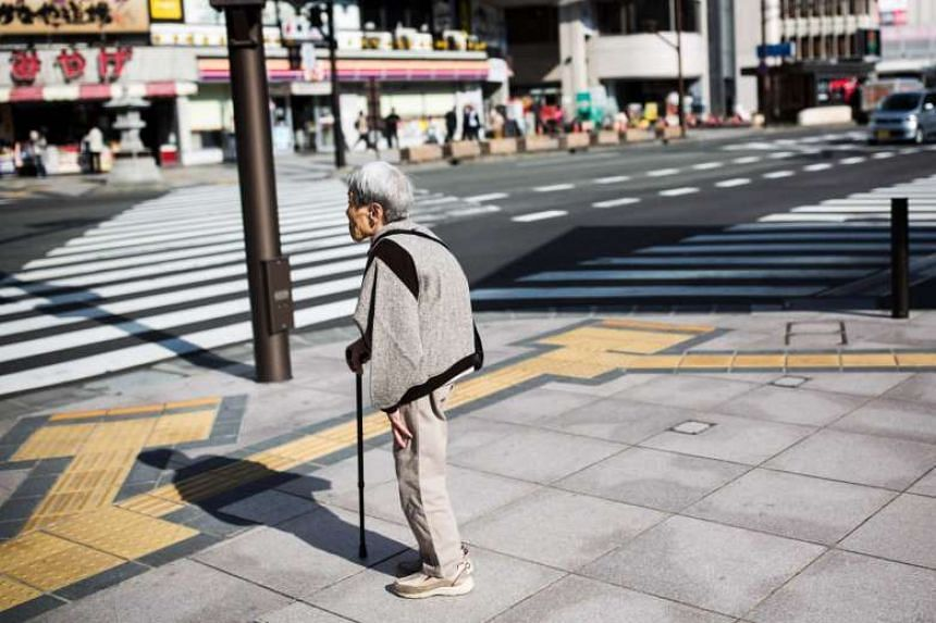 A Japanese elderly woman waits for the traffic light to cross the street in Nagano, north-west of the capital Tokyo, on Nov 7, 2016.