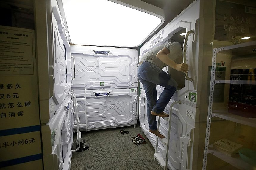 A man entering a capsule bed unit in Beijing. Each napping pod is equipped with an electric fan, reading light and USB port. Users get a disposable bedsheet, pillow cover and blanket before they enter the capsule.