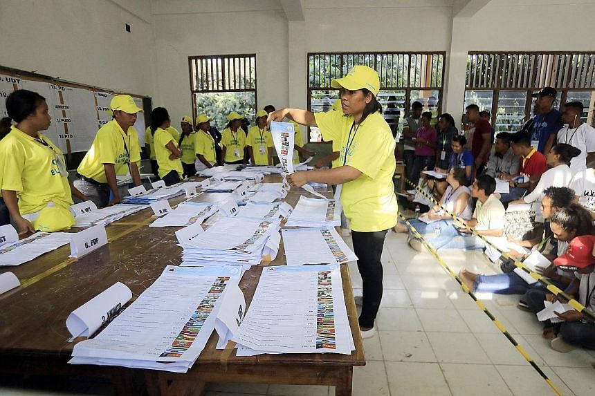 Election workers checking votes during the parliamentary polls in Dili, Timor Leste, over the weekend. More than 700,000 people had registered to vote, and the official result will be announced by Aug 6.