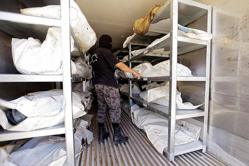 A member of Libya's anti-crime service in a morgue in Misrata where the bodies of foreign ISIS militants are stored. Hundreds of bodies foreign militants still lie in freezers as the authorities negotiate with other governments to decide what to do w