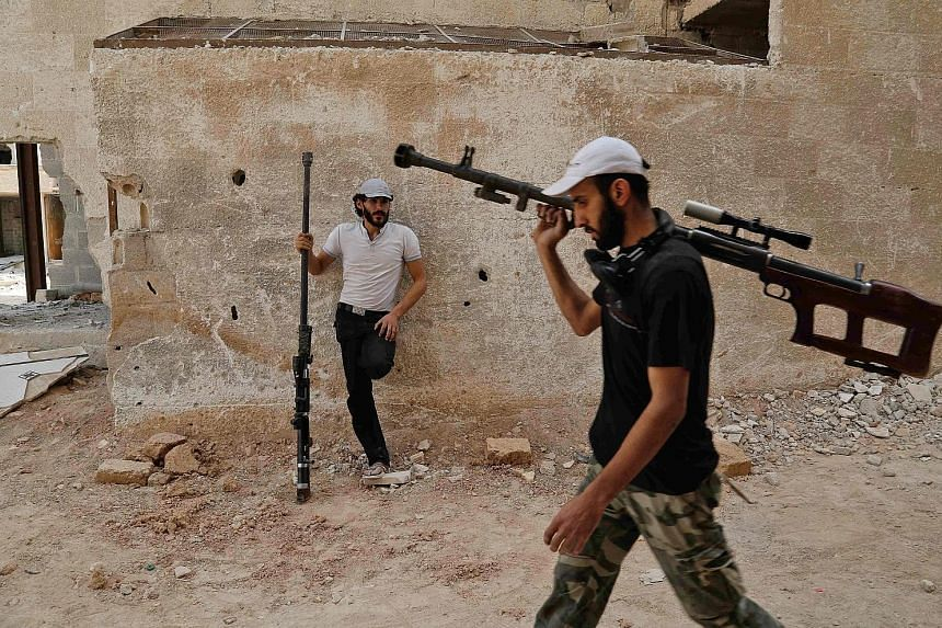 Rebel fighters carrying homemade sniper rifles in Ain Terma last Thursday. The militant stronghold east of Damascus was reportedly bombarded by regime warplanes yesterday, even though a ceasefire had been announced the day before. No casualties were