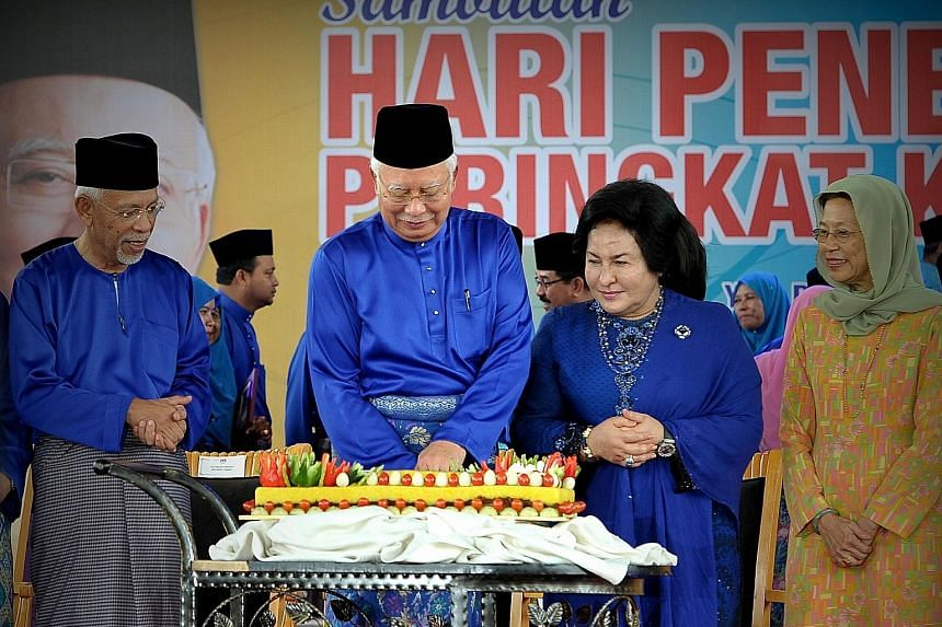 Above: Mr Najib Razak and his wife, Datin Seri Rosmah Mansor, with a traditional pulut kuning (Malay glutinous rice) cake at the Felda event in Putrajaya. He later cut the cake to celebrate his 64th birthday. Right: Felda landowners cheering the anno