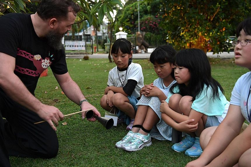 Children from the Japanese town of Hirono - (from left) Yumi Koretsugu, Kotoha Watanabe, Saito Rin and Sayo Ochiai, all 10 - listen as instructor Desmond Hinkson demonstrates the agogo, an instrument used in the Brazilian martial art capoeira, which