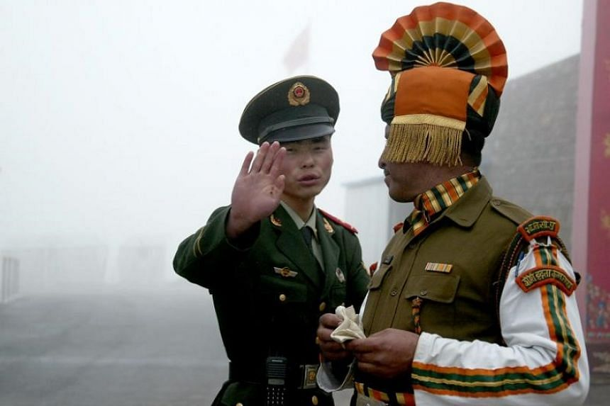 A July 10, 2008, file photo of a Chinese soldier (left) next to an Indian soldier at the Nathu La border crossing between India and China in India's north-eastern Sikkim state.