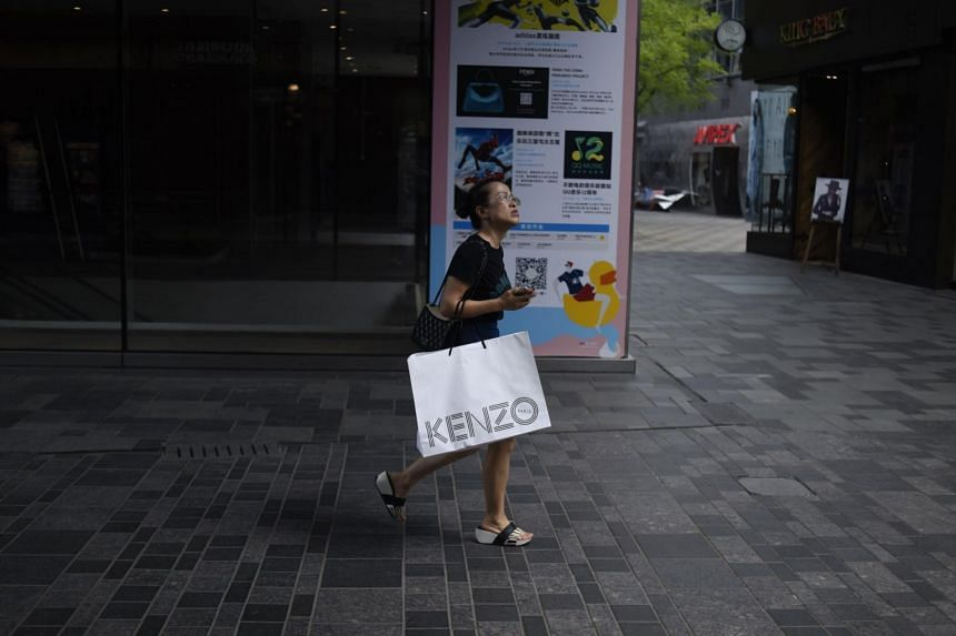 A woman carrying a shopping bag looks on as she walks past a store in Beijing on July 13, 2017.