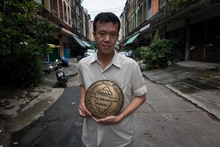 Thai dissident Ekachai Hongkangwan with a brass replica of the missing plaque commemorating the year Thailand went from being an absolute monarchy to a democracy in 1932, outside his house in Bangkok, on July 12.