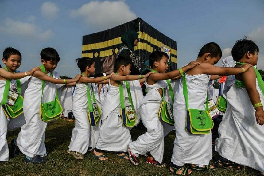 Malaysian children taking part in a practice run for the Muslim haj pilgrimage on Monday (July 24), walking round a model of the holy Kaaba shrine.
