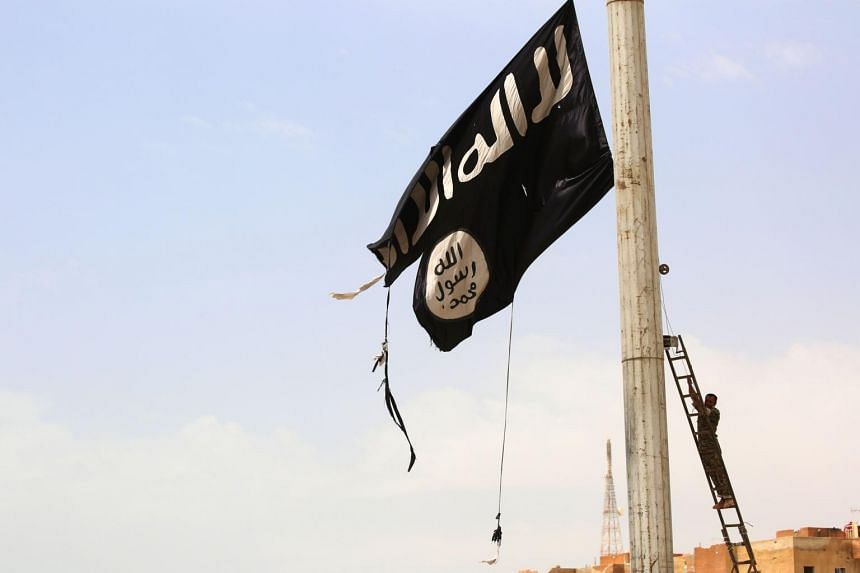 A member of the US-backed Syrian Democratic Forces removes an ISIS flag in Syria on April 30, 2017.