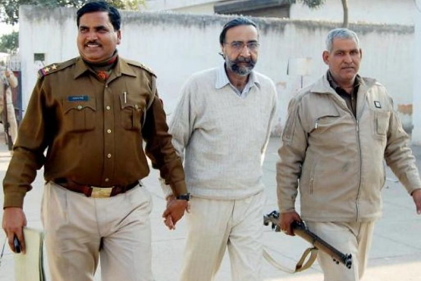 Moninder Singh Pandher (C), joint accused in a case involving the gruesome deaths of 19 people, is escorted to court in Ghaziabad on the outskirts of New Delhi on February 12, 2009. An Indian court convicted a businessman and his domestic employee of