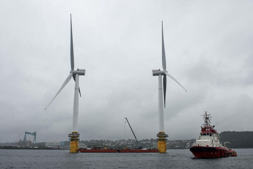 Barges position offshore floating wind turbines during assembly in the Hywind pilot park, operated by Statoil ASA, in Stord, Norway, on Friday, June 23, 2017. The world's first offshore floating wind farm will be moved to its final destination outsid