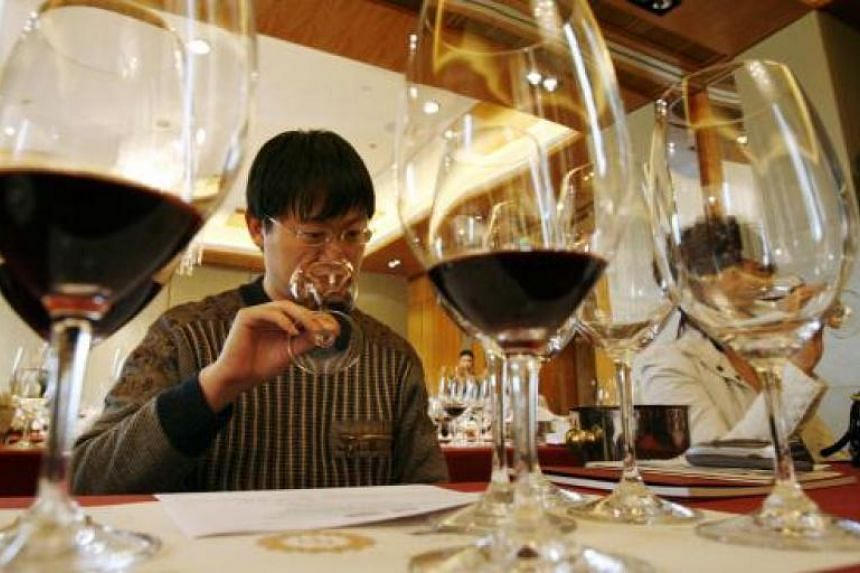 A file picture of a wine critic smelling red wine during a wine-tasting event in Beijing. PHOTO: REUTERS