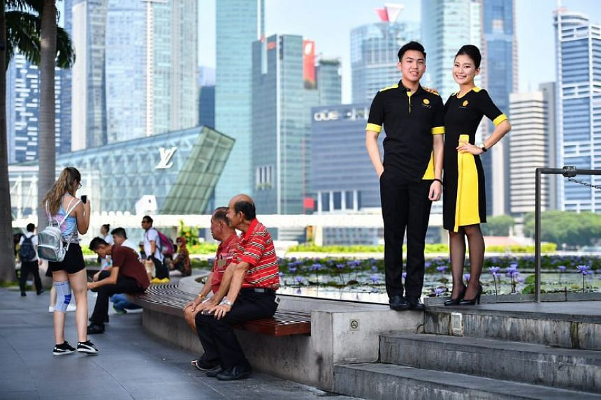 Scoot cabin crew Wee Gim Shawn, 20 (left), and Shin Heeja, 26, in their new outfits.