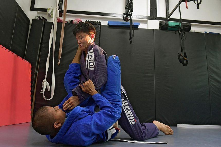 Ms Marilyn Cheng learning to pin down an opponent during her Brazilian jiu-jitsu class.