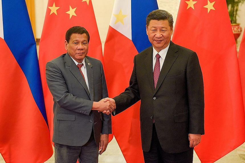 Remains of a victim of the Marawi siege at a mass burial in Marawi yesterday. Philippine President Rodrigo Duterte with his Chinese counterpart Xi Jinping in Beijing recently. Mr Duterte's tax reforms aim to fund his S$215 billion infrastructure prog