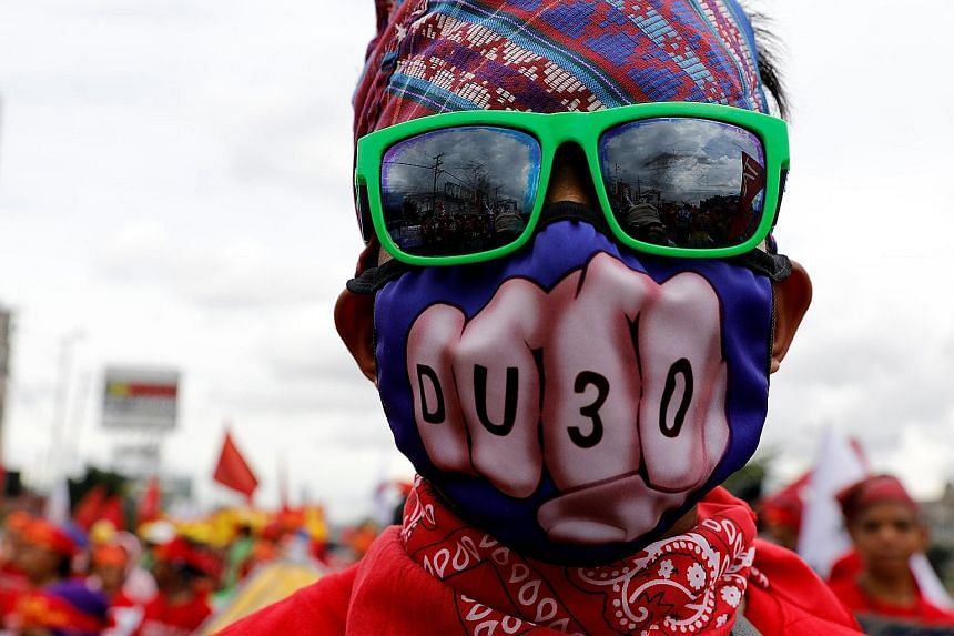 An anti-government protester, wearing a mask that plays on Mr Rodrigo Duterte's name, taking part in a march towards the Philippine Congress ahead of the President's second State of the Nation address yesterday.
