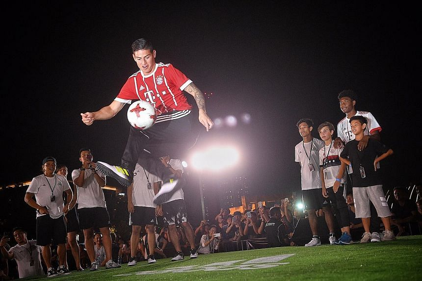 Bayern's new man James Rodriguez displaying his skills in front of fans, as team-mate David Alaba (right) looks on at Clifford Square during the adidas Football Freestyle Battle last night.