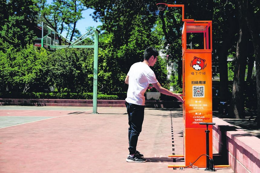 Enterprising businesses are making convenience their selling point as they offer users instant access to almost anything they need or lack, from umbrellas in Shanghai (far left) to basketballs at a Beijing university (left). A customer in Shanghai sc