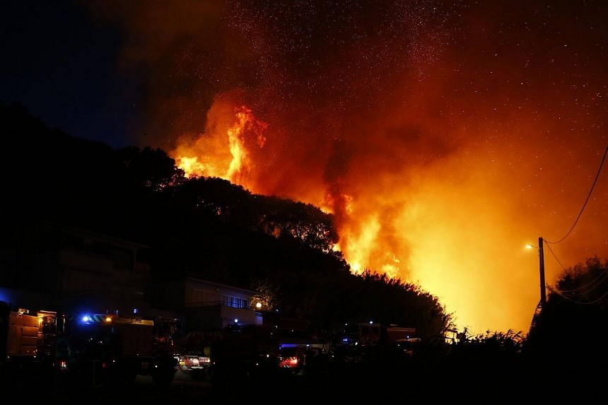 Firefighters gather at the site of a fire in Biguglia on the French Mediterranean island of Corsica, on July 24, 2017.