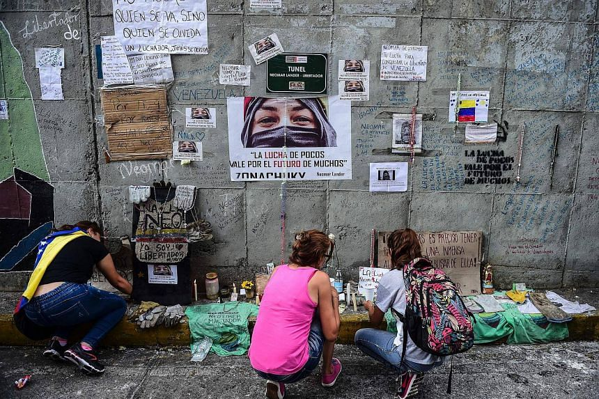 Opposition demonstrators make an altar on the site where young activist Neomar Lander was mortally wounded during clashes with riot police, in Caracas, on July 24, 2017.