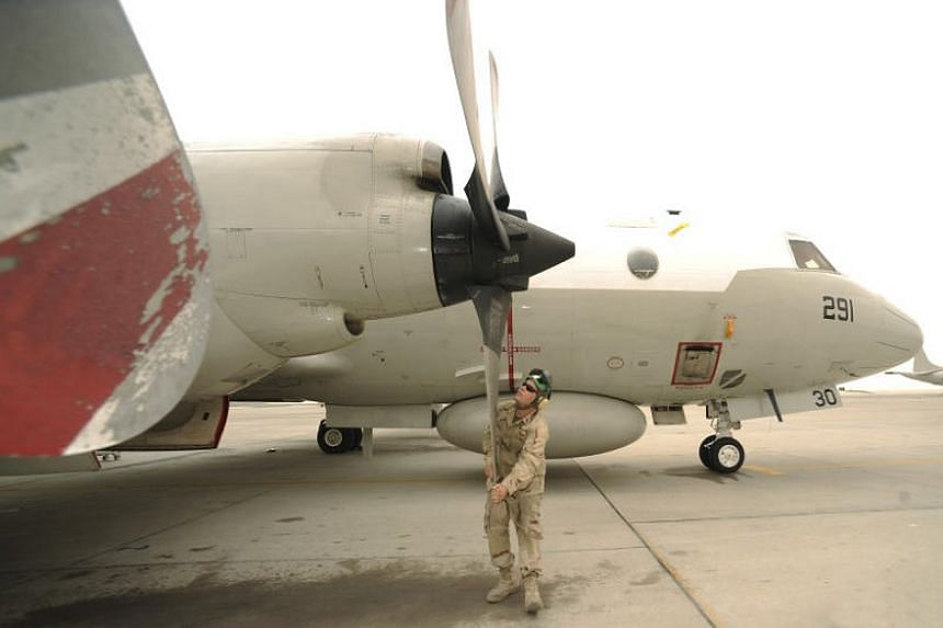 In an undated handout photo, a Navy officer performs a pre-flight propeller inspection on an EP-3 surveillance plane in 2011. A US Navy EP-3 plane had to take evasive action to avoid crashing into a Chinese fighter jet above the East China Sea on Jul