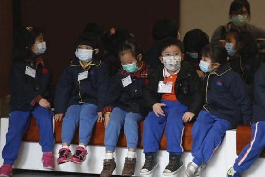 In this file photo, young students, wearing masks to prevent flu, visit the Legislative Council on a school trip in Hong Kong.