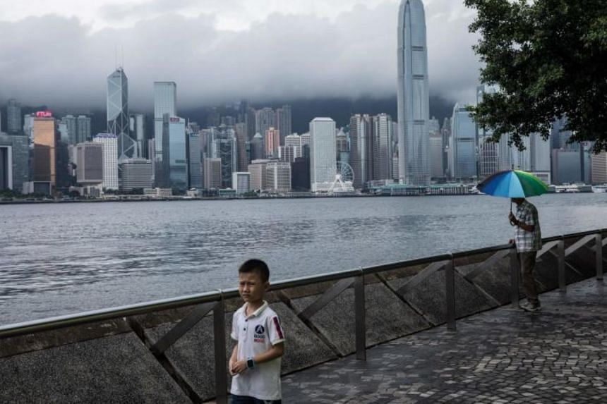 People walk along a promenade before the city skyline in Hong Kong on July 23, 2017.