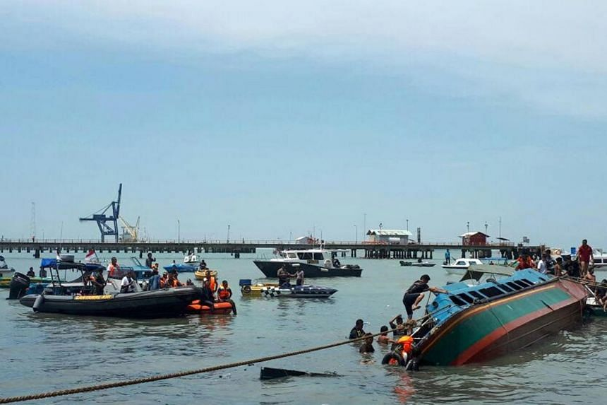 Rescuers and residents search for victims of a capsized speedboat in the water off Tarakan, on July 25, 2017.