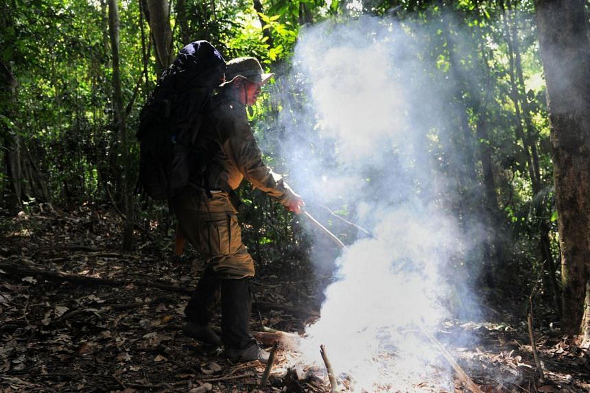 A forest ranger putting out a fire found along a trail in the Leuser ecosystem rainforest in Indonesia.
