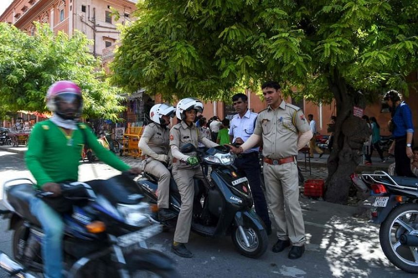 Members (centre) of a newly launched female police patrol unit talk to traffic police as they patrol through the old market in Jaipur on June 14, 2017.