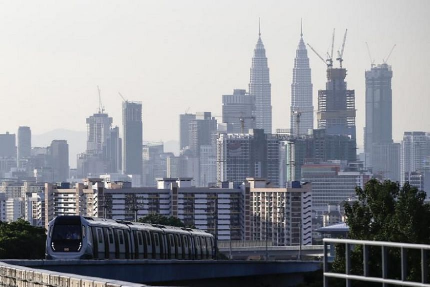 A train travels against a backdrop of the capital city of Kuala Lumpur on the second phase of the first Mass Rapid Transit (MRT) Line at Kajang, Malaysia, on July 17, 2017.