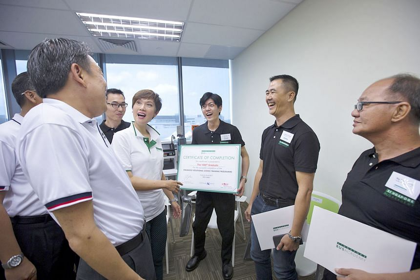 Mrs Josephine Teo and some of the bus captains chatting with Mr Melvin Yong (at left) at the graduation ceremony yesterday. SBS Transit trainee bus captain Aw Wei Han (centre) is the academy's 1,000th bus captain to pass the enhanced vocational train