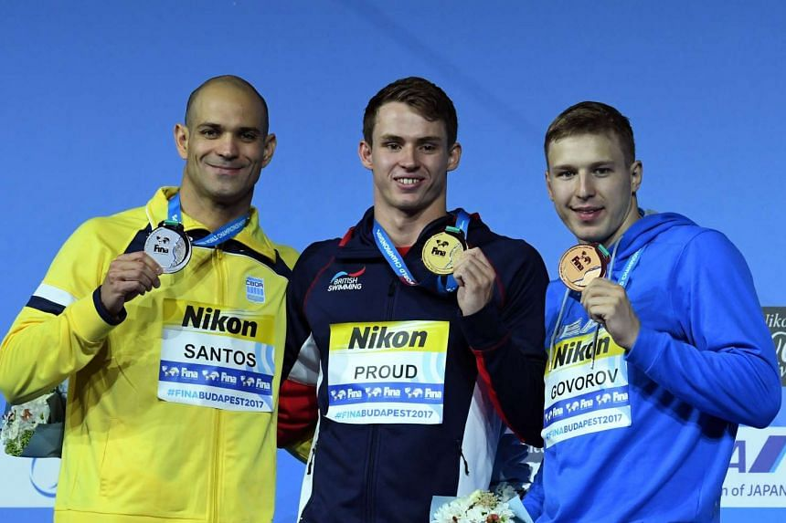 Brazil's Nicholas Santos, Britain's Benjamin Proud and Ukraine's Andrii Govorov celebrating on the podium after the 50m butterfly final during the swimming competition at the 2017 Fina World Championships in Budapest, on July 24, 2017.