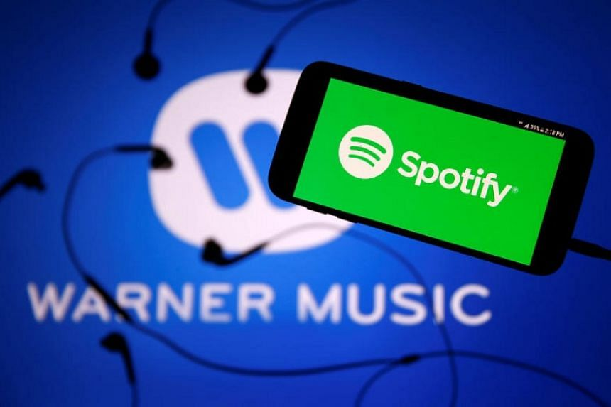 A smartphone with a headset with Spotify logo is seen in front of a displayed Warner Music logo in this illustration picture taken on July 24, 2017.