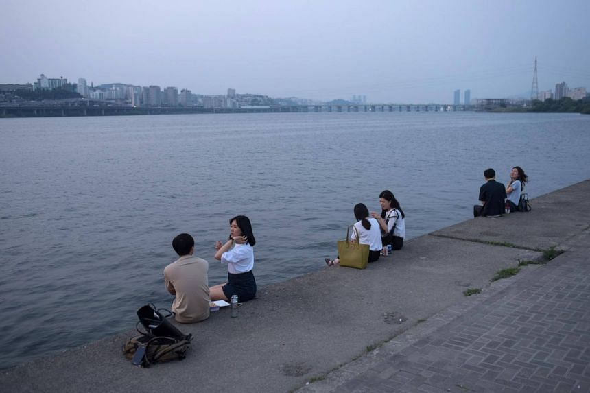 People sitting by the Han river in Seoul on June 16, 2017.