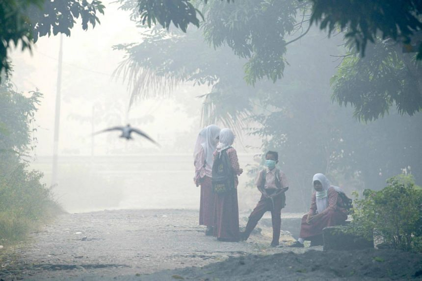Acehnese schoolchildren wait for their bus to school in Meulaboh, Aceh province on July 26, 2017.