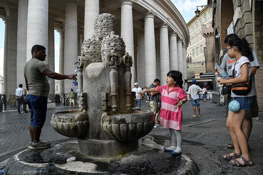People filling their water bottles from a fountain near Saint Peter's Square, just outside Vatican city. Lower-than- average rainfall in Rome has forced the city to turn off fountains and consider the prospect of water rationing.